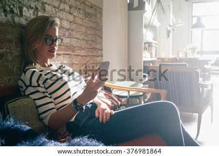 attractive girl chatting with her friends while sitting in a coffee-shop.attractive businesswoman check e-mail on her smart-phone.  - stock photo