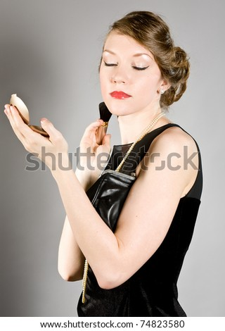 attractive girl does to itself a make-up of the person - stock photo