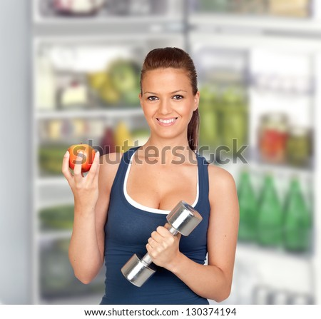 Attractive girl eating a apple of de fridge after training - stock photo