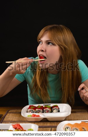 attractive girl eating rolls at the table