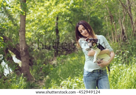 Attractive girl embracing Jack Russel Terrier. Background of majestic natural landscape - stock photo