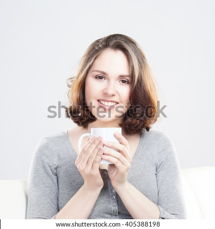 Attractive girl enjoying a cup of coffee at home.