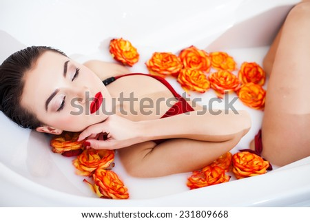 Attractive girl enjoys a bath with milk and rose. - stock photo
