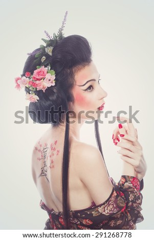 Attractive girl geisha. Drawing cherry and hieroglyphs on the back. The concept of Asian beauty. - stock photo