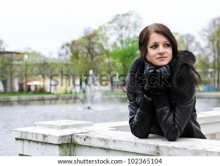 Attractive girl girl standing near a pond in the park