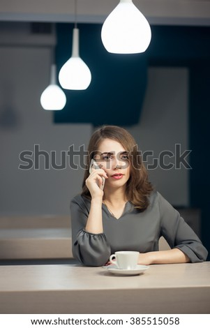 attractive girl has a cup of tea in restaurant and has a conversation by smartphone;