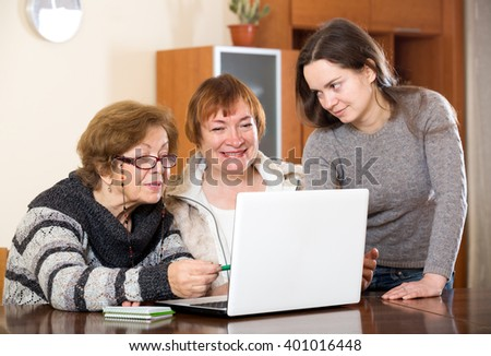 Attractive girl helping senior women buy something in web - stock photo