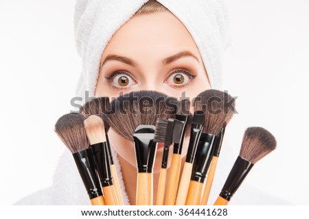 Attractive girl hiding behind makeup brushes - stock photo