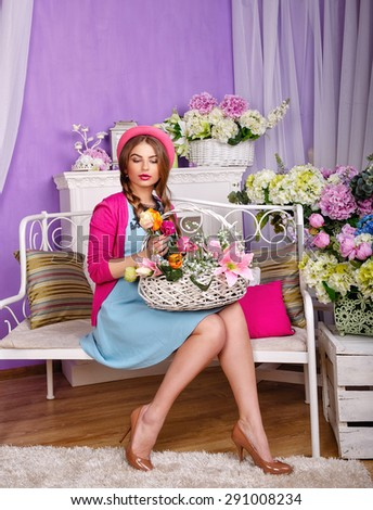 Attractive girl holding a basket of flowers. The girl sitting on a bench. The concept of innocent beauty. - stock photo
