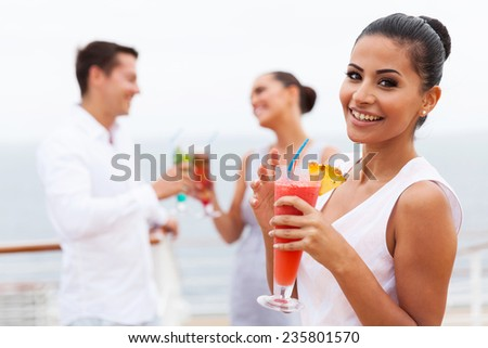 attractive girl holding a tropical cocktail on cruise - stock photo