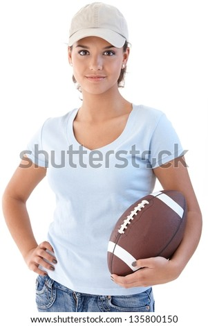 Attractive girl holding American football, looking at camera. - stock photo