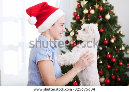 Attractive girl holding dog and enjoy in christmas holiday - stock photo