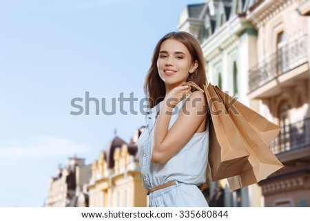 Attractive girl holding shopping bags and posing for the camera - stock photo