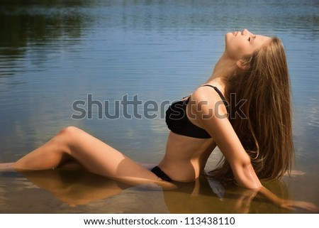 Attractive girl in a bikini relaxing by the river - stock photo