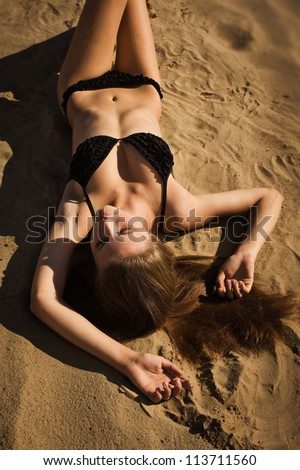 Attractive girl in a bikini relaxing on a sandy beach - stock photo
