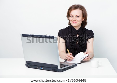 attractive girl in a black dress with a laptop at the table