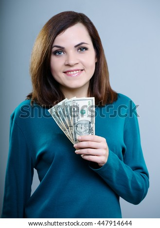 attractive girl in a blue T-shirt holds a money on a gray background