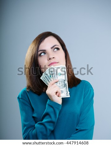 attractive girl in a blue T-shirt holds money near the face, on a gray background - stock photo