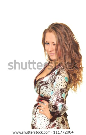 Attractive girl in a dress with long brown wavy hair winks. Isolated on white background