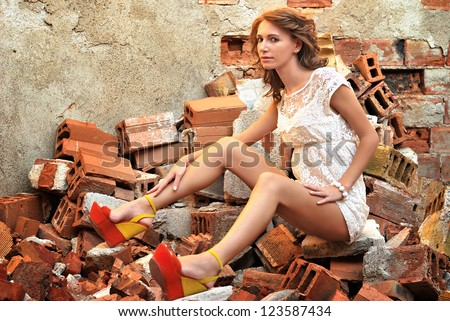 Attractive girl in a provocative pose next to a brick wall - stock photo