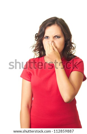 Attractive girl in a red shirt from the stench covers the nose. Isolated on white background