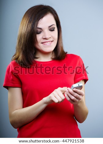 attractive girl in a red shirt writing a message on the phone and smiling