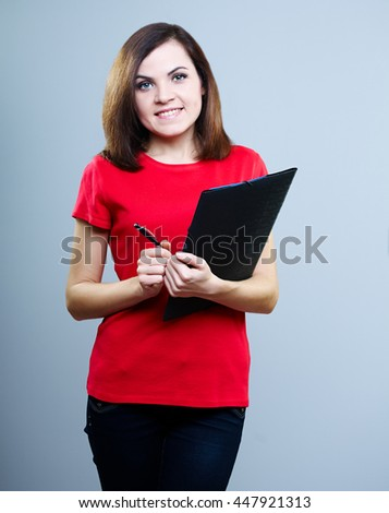 attractive girl in a red T-shirt and jeans holding a folder and pen, on a gray background