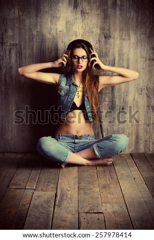 Attractive girl in casual jeans clothes listens to music in headphones. Fashion. - stock photo