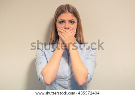 Attractive girl in classic clothes is covering her mouth and looking at camera, against gray background - stock photo