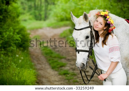 Attractive girl in floral wreath with horse