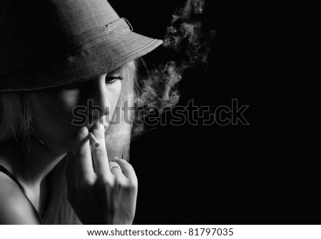 Attractive girl in hat smoking a cigar