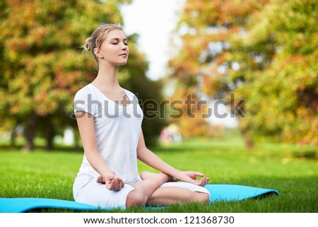 Attractive girl in lotus pose outdoors - stock photo