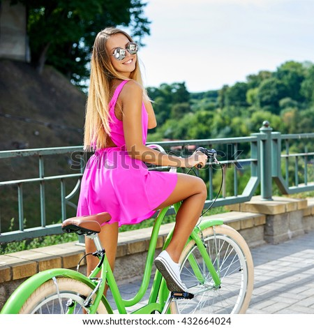 Attractive girl in pink dress with bike on a street - stock photo