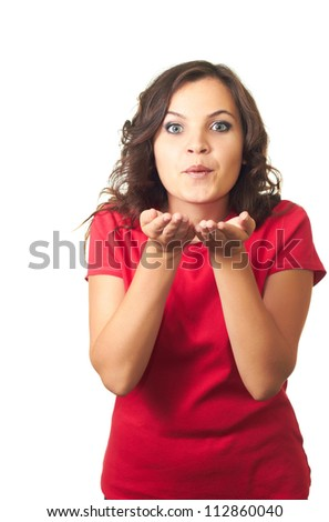 Attractive girl in red shirt blowing a kiss at you. Isolated on white background