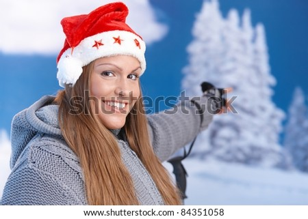 Attractive girl in santa hat, dressed up warm, pointing to winter landscape, smiling.? - stock photo
