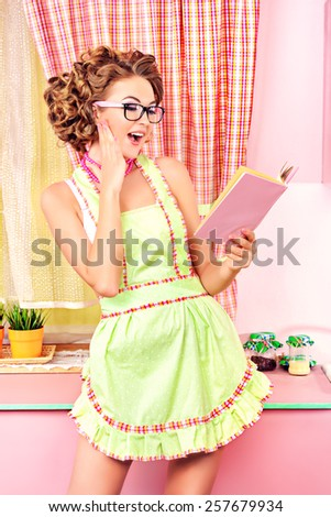 Attractive girl in sexy lingerie  and apron alluring on her glamorous pink kitchen. Fashion.  - stock photo