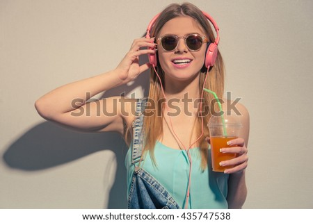 Attractive girl in summer clothes and headphones is holding a glass of juice, looking at camera and smiling, against gray background - stock photo
