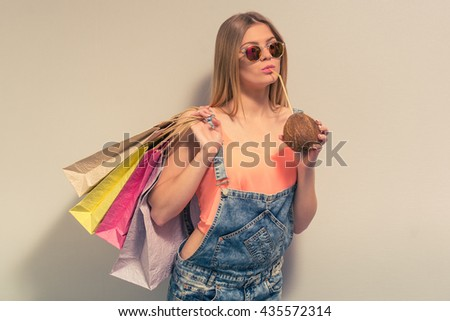 Attractive girl in summer clothes and sun glasses is drinking a coconut milk, holding shopping bags and looking at camera, against gray background - stock photo