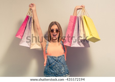 Attractive girl in summer clothes and sun glasses is holding shopping bags, looking at camera and smiling, against gray background - stock photo