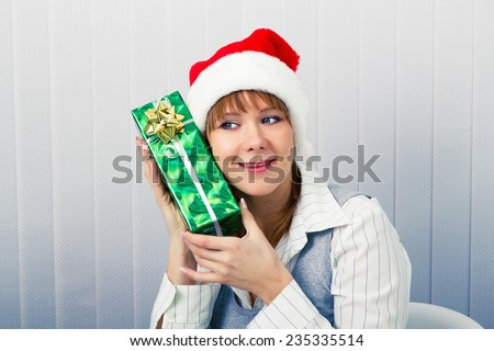 Attractive girl in the office in Santa hats with a gift - stock photo