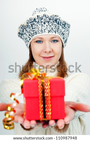 Attractive girl in winter hat gives a wrapped gift - stock photo