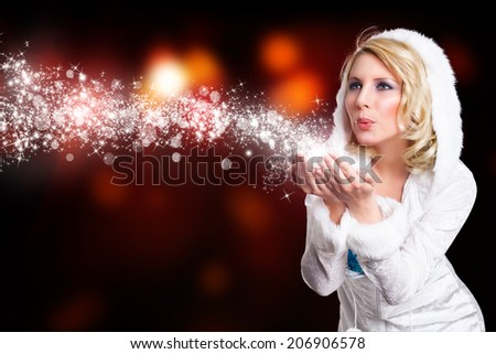attractive girl in winter outfit blowing twinkling stardust - stock photo