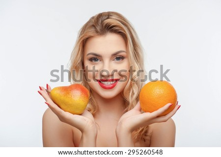 Attractive girl is holding orange in one hand and pear in another. She is smiling happily. Isolated on background - stock photo