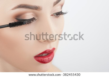 Attractive girl is putting on make-up - stock photo