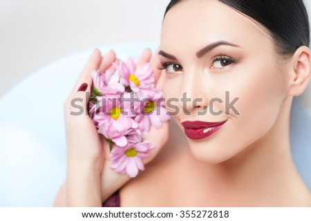 Attractive girl is relieving stress in a bath. She is lying and smiling. The lady is holding flowers near her face and looking at camera happily - stock photo