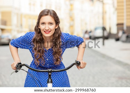 Attractive girl is riding a bicycle with enjoyment. She is smiling and looking forward with happiness. Copy space in right side - stock photo