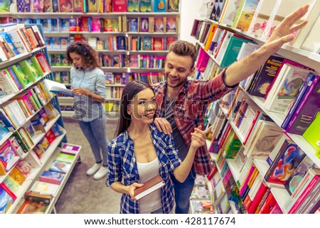 Attractive girl is smiling and asking handsome guy to take book from upper shelf in the bookshop, another girl in the background - stock photo