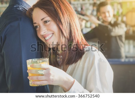 Attractive girl is smiling and drinking cocktail supported by her boyfriend - loving couple-  during a party - caucasian people - love, party, drink and people concept - stock photo