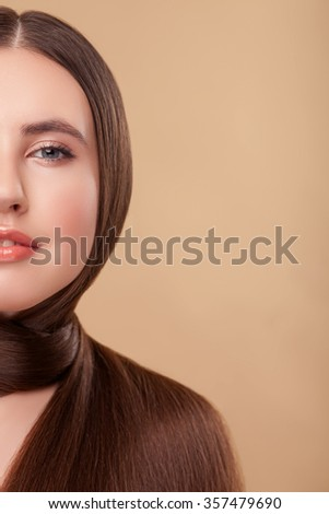 Attractive girl is winding her strong flexible hair around her neck. She is looking forward and smiling. Isolated and copy space in right side - stock photo