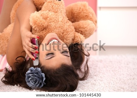 Attractive girl laying on floor at home, hugging huge teddy bear, chatting on mobile. - stock photo